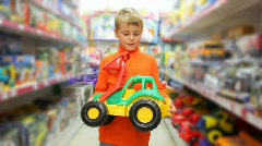boy examines toy excavator in store - stock footage