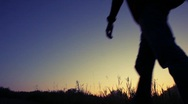 Silhouette of man walks uphill against sky Stock Footage