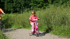 Girl sits on bicycle, woman rides pass in park Stock Footage