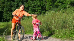 Mother pats on the back daughter, then both of them rides bicycles Stock Footage