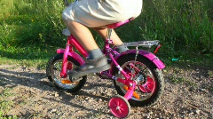 Boy pedaling on bicycle in park, girl pushes him Stock Footage