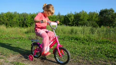 Girl treadling stopped bicycle, boy rides to her Stock Footage