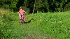 Girl rides bicycle to camera in park Stock Footage