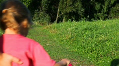 Parents helps a kids riding bicycles from camera in park Stock Footage
