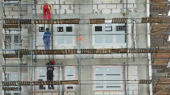 Builders works on falsework in building area Stock Footage
