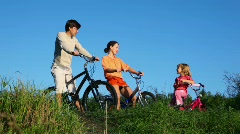Family with daughter sits on bicycles and talks Stock Footage