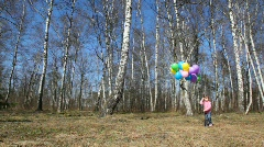 Girl with bunch of balloons walks in forest Stock Footage