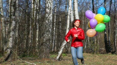 Woman with balloons runs in spring grove Stock Footage