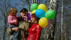 Family with bunch of balloons in forest Stock Footage