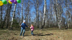 Boy holds balloons and girl runs around Stock Footage