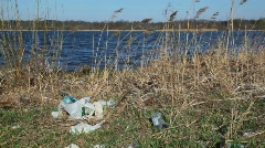 Household rubbish on bank of river Stock Footage