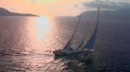 Stock Video Footage of An aerial of a magnificent sailing ship silhouetted against the sun.