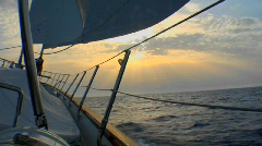 A shot of the side of a sailboat heading into the sunset. Stock Footage