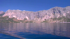 View from a sailboat motoring along a glassy ocean with mountainous crestline in - stock footage