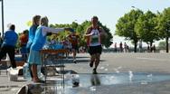 Participants of Riga international marathon run past a refreshment station Stock Footage