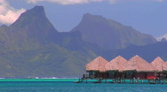 Stock Video Footage of Tahitian huts on the water with mountain peaks in the background as rowers pass