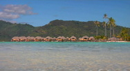 Stock Video Footage of Tahitian huts on the water with lush mountains in the background.