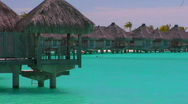 Stock Video Footage of Tahitian huts rest over turquoise water.