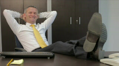 Relaxed businessman in office (sequence) - stock footage