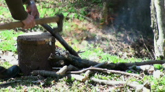 Cutting wood in the forest near a fire Stock Footage