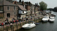 Stock Video Footage of Boats moored on the river Ouse with people on the quayside in the city of York