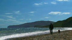 A man walks his dog at sea Stock Footage