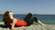 Woman lies near the sea Stock Footage