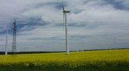 Wind turbines and electric wires in a rapeseed field Stock Footage
