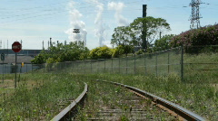 Train tracks with Industrial factory and discharge Stock Footage