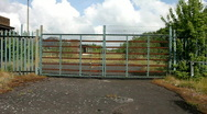 Locked gates and vandalised office of a closed steel works Stock Footage