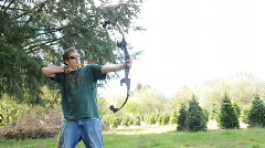 Man Casually Practicing Archery with Bow and Arrow Outside Stock Footage