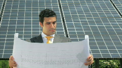 Businessman reading blueprints in solar power station (series) Stock Footage