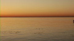 Fishing boat at sunrise - wide pan left to right Stock Footage