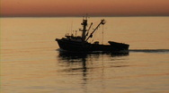 Stock Video Footage of Fishing boat at sunrise - moves right to left