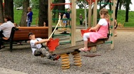 Boy and girl on seesaw Stock Footage
