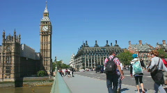 Tourists walk towards Big Ben and the Houses of Parliament London England Stock Footage