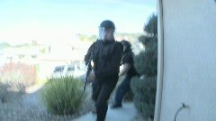 DEA officers with arms drawn perform a drug raid on a house. - stock footage