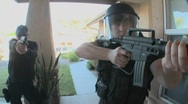 Stock Video Footage of DEA officers with arms drawn perform a drug raid on a house.
