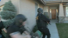 DEA officers with arms drawn perform a drug raid on a house. Stock Footage