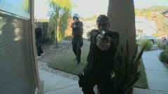 DEA or SWAT officers with arms drawn pound on the door before performing a drug Stock Footage