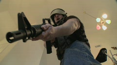 A SWAT team with DEA officers clears a house during a drug raid and holds a Stock Footage