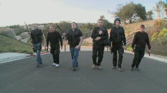 A SWAT team of DEA agents walks in a macho way up a street in a display of - stock footage