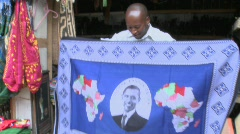 A vendor holds up a blanket with Barack Obama picture on it in kenya. Stock Footage