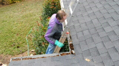 Man Cleaning Gutters on a Windy Day Stock Footage