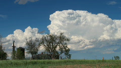 Churning Cumulus Clouds behind Farm - stock footage