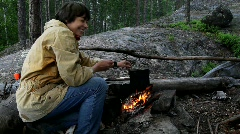 Woman in tarpaulin jacket and jeans cook on bonfire in forest Stock Footage