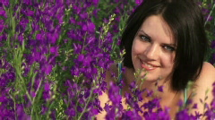 Girl is among the purple flowers Stock Footage