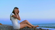 A girl listens to music on the sea Stock Footage