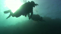 Stock Video Footage of Two scuba divers swim past camera silhoutted by the Sun