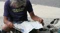 Homeless man reads newspaper Footage